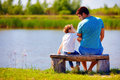 Happy Father And Son Sitting On The River Bank Royalty Free Stock Images - 54433679