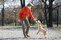 Girl In Orange Jacket Plays With Puppy Royalty Free Stock Photos - 54476808
