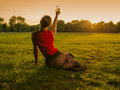 Woman Lifting Bottle To Sunset In Park Royalty Free Stock Photos - 54484558