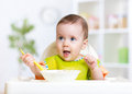Happy Baby Kid Eating Food Itself With Spoon Royalty Free Stock Photo - 54644285