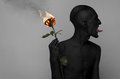 Gothic And Halloween Theme: A Man With Black Skin Holding A Red Rose, Black Death Isolated On A Gray Background In Studio Stock Images - 54649394