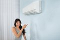 Woman Holding Remote Control Air Conditioner Royalty Free Stock Photos - 54658578