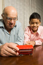 Grandfather And Grandson Sitting At The Table Royalty Free Stock Photography - 5479427