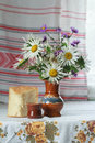Still Life Of Ceramic Vase And Glass With Cut Lilac And White Aster Flowers And Slice Of Yeasted Wheat Bread Royalty Free Stock Image - 54769726