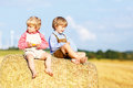 Two Little Friends And Friends Sitting On Hay Stack Royalty Free Stock Photos - 54830918