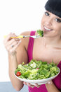 Young Healthy Woman Eating A Fresh Bowl Of Green Salad Leaves Stock Image - 54864181