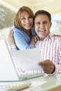 Senior Hispanic Couple Working In Home Office Royalty Free Stock Image - 54948266