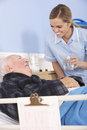 Nurse Giving Glass Of Water To Senior Man In Hospital Stock Photos - 54956573