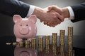 Businesspeople Shaking Hands With Coins And Piggybank Royalty Free Stock Image - 54964086