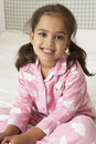 Young Girl Wearing Pajamas Sitting On Bed Stock Image - 54966911