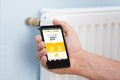 Person Hand Adjusting Temperature Of Thermostat Using Cellphone Royalty Free Stock Image - 54967986