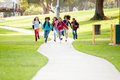 Group Of Children Running Along Path Towards Camera In Park Stock Image - 54982601