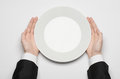 Business Lunch And Healthy Food Theme: Man S Hand In A Black Suit Holding A White Empty Plate And Shows Finger Gesture On An Isola Royalty Free Stock Photos - 54999938