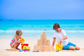 Cute Kids Building Sand Castle On The Beach Stock Photography - 55005122