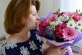 Woman Smelling A Bouquet Of Flowers Stock Images - 55030164