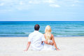 Loving Couple Sitting And Embracing On The Beach Royalty Free Stock Photo - 55073015