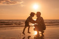 Father And Son Playing On The Beach At The Sunset Time. Royalty Free Stock Photo - 55147785