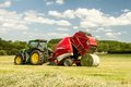 A Round Baler Discharges A Hay Bale During Harvesting Stock Photos - 55180843