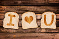 I Love You Written On Toasted Slices Of Bread, On Wooden Planks Background Stock Images - 55191534