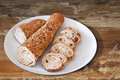 Sliced Integral Baguette Bread Elongated Loaf On White Porcelain Plate Set On Old Weathered Cracked Flaky Wooden Table Royalty Free Stock Image - 55220946