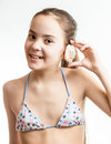 Smiling Girl Posing With Seashell Next To Ear Stock Photography - 55267342