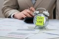 Businessman With Tax Time Reminder Note On Alarm Clock Stock Image - 55352591