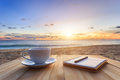 Coffee Cup On Wood Table At Sunset Or Sunrise Beach Royalty Free Stock Photo - 55391425