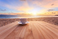 Coffee Cup On Wood Table At Sunset Or Sunrise Beach Royalty Free Stock Image - 55391436