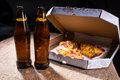 Beer Bottles On Table By Pizza Box With Open Lid Royalty Free Stock Photos - 55427258