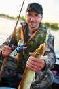 Fisher With Catch Pike On River Royalty Free Stock Images - 55549559