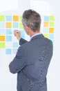 Puzzled Businessman Looking Post Its On The Wall Stock Photos - 55559363