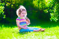 Little Girl Eating Ice Cream In The Garden Royalty Free Stock Image - 55568256