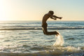 Man Jumping On Beach At Sunset Stock Images - 55574634