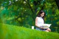Young Woman Relaxing With Coffee In Park Reading A Royalty Free Stock Image - 55620536