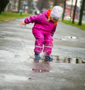 Little Happy Girl Jumping In Puddle Royalty Free Stock Images - 55676309