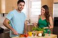 Happy Healthy Young Vegan Couple Cooking Vegetables At Home Royalty Free Stock Image - 55802386