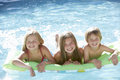 Group Of Children Relaxing In Swimming Pool Together Stock Images - 55890764