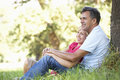 Middle Aged Couple Relaxing In Countryside Leaning Against Tree Stock Image - 55891851