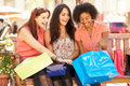 Three Female Friends With Shopping Bags Sitting In Mall Stock Photos - 55901613