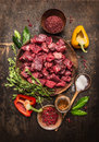 Raw  Uncooked Meat Sliced In Cubes With Fresh Herbs, Vegetables And Spices On Rustic Wooden Background, Ingredients For Beef Stew Stock Photos - 55977683