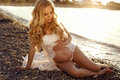Beautiful Pregnant Woman With Long Blond Hair Posing On Sunset Beach Royalty Free Stock Photo - 56058105