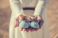 Woman Hands Holding A Pair Of Baby Shoes Stock Photos - 56095673