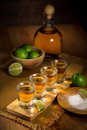 Tequila Shots Grouped Together With A Bottle And Cut Limes On A Restaurant Bar Table Stock Photo - 56132570