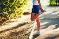 Yong Sporty Woman Streching Her Leg Royalty Free Stock Photography - 56179657