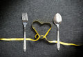 Fork And Spoon With Heart Shape Made From Yellow Ribbon On Black Royalty Free Stock Images - 56227409