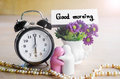 Flowers In A Ceramic Pots With Purple Vintage Alarm Clock. Stock Photos - 56342533