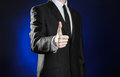 Business And The Presentation Of The Theme: Man In A Black Suit Showing Hand Gestures On A Dark Blue Background In Studio Isolated Stock Photography - 56345492