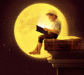 Cute Little Boy Reading A Book In The Moon Light Stock Images - 56419914