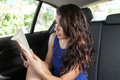 Young Woman In Back Seat Of Car Reading Paperback Royalty Free Stock Image - 56420346
