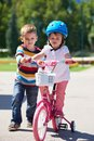 Boy And Girl In Park Learning To Ride A Bike Stock Images - 56433884